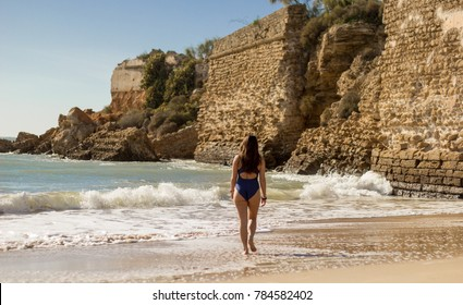 A young beautiful female model enjoying a photo session in Cadiz. A swimsuit brunette model near a castle in ruins in Cadiz. Beautiful latin girl in swimsuit