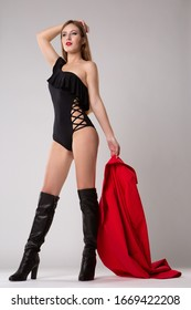 a young beautiful female model poses in a black sexy bodysuit and high heeled boots holding a bright red raincoat in her hand