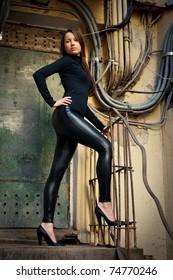 Young beautiful female model standing before old rusty door