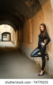 Young beautiful female model standing near old wall