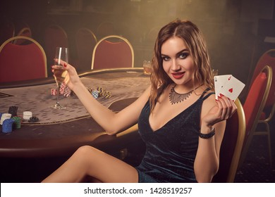Young beautiful female is posing sitting on a chair against a poker table in luxury casino.