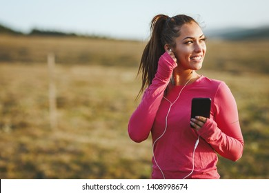 Young beautiful female runner listening to music and preparing to jogging at morning in mountains.