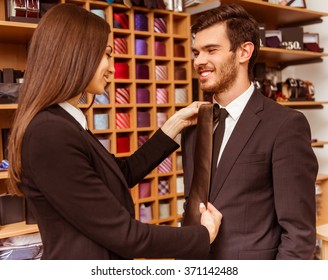 Young beautiful female shop assistant smiling and offering a tie to a modern young handsome businessman in the suit shop
