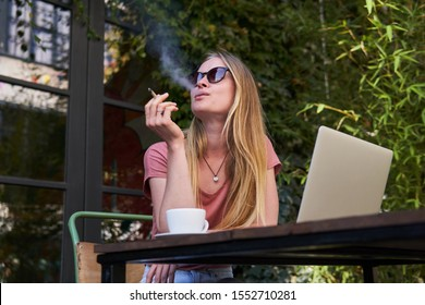 Young beautiful female sitting at a street cafeteria with a laptop on a table and smoking marijuana joint