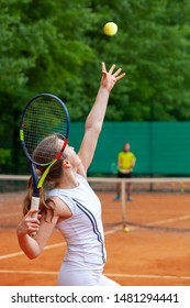 Young beautiful female tennis player serving.