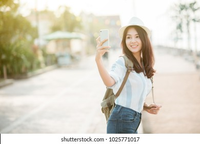 Young beautiful female traveler in the city and using smart phone for take a photo