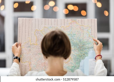 Young beautiful female traveler standing on the street with window and light. Trendy look searching direction on location map while traveling abroad.