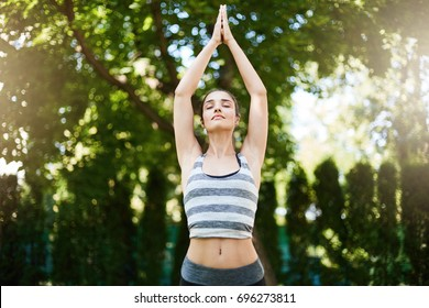Young beautiful female yoga teacher starting her healthy day in her backyard or a park.