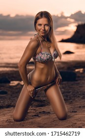 Young beautiful fit trained tanned female model posing on the beach in the evening sunset light
