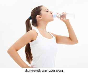 Young beautiful fit woman drinking water after exercise.