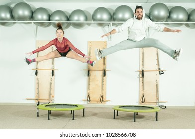 Young beautiful fitness couple workout extreme acrobatic exercise on trampoline jumps as preparation for the competition, selective focus with motion blur
