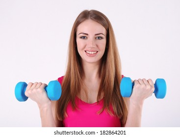Young beautiful fitness girl exercising with dumbbells in gym