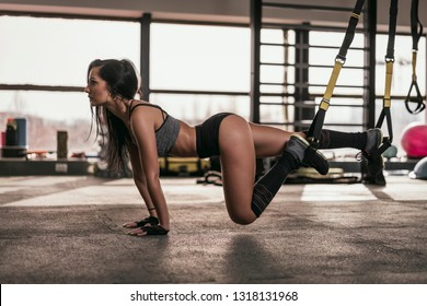 Young beautiful fitness woman exercise in the gym. Female doing workout. Sexy girl training hard