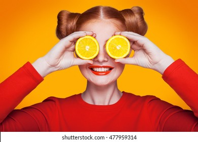 Young beautiful funny fashion model with lemon slice on orange background. with makeup and hairstyle and freckles. holding lemon between eyes with toothy smile.