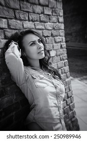 Young beautiful girl against old stone wall, outdoor shot. Black and white picture.