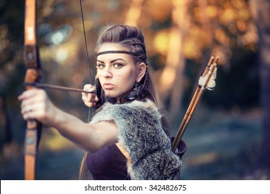 The young beautiful girl amazon aiming a bow while hunting in the forest, mythical character, a fairy tale, the legend