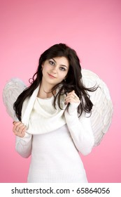 Young beautiful girl in angel suit over pink background.