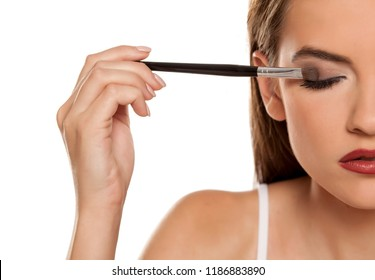 young beautiful girl apllying eyeshadow with makeup brushe on white backgeound