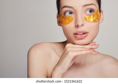 Young beautiful girl applying golden collagen patches under her the eyes. Removing wrinkles and dark circles. A woman takes care of delicate skin around her eyes. Cosmetic procedures. Facial skin care
