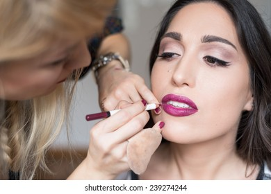 Young beautiful girl applying make up by makeup artist