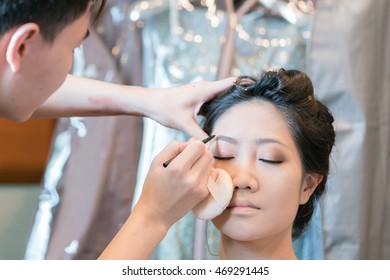 Young beautiful girl applying make-up by make-up artist