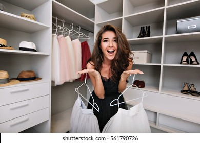 Young beautiful girl asks for help in choosing clothes in a dressing room. She smiles and looks in camera. She's dressed in black dress . Expressing true positive face emotions