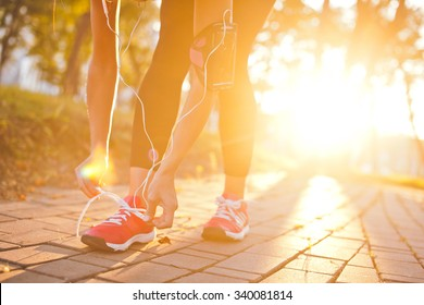 Young beautiful girl athlete with armband and earphones listening to music and tying laces during training with sunset and sunbeam on background. Copy space. Bright and warm photo