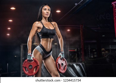 Young beautiful girl athlete bodybuilder does exercises in the modern gym. Concept - the power of beauty, fashion, diet, sports nutrition, sportswear.