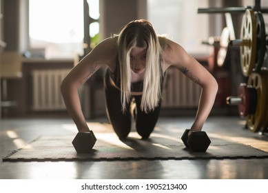 Young beautiful girl athlete does push-ups in the fitness room.