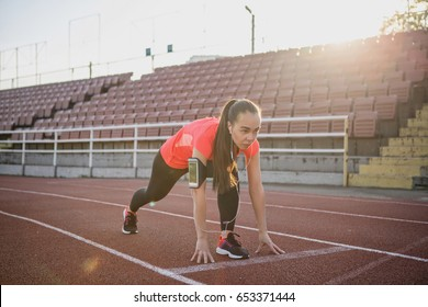 Young, beautiful girl athlete in sportswear is running at the stadium