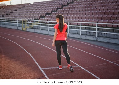 Young, beautiful girl athlete in sportswear stands at the stadium
