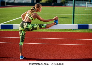 Young, beautiful girl athlete in sportswear doing warm-up at the stadium