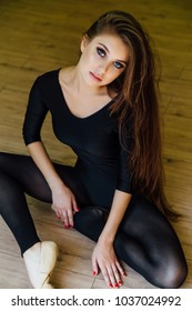 Young beautiful girl ballet dancer sits on the floor in the studio for dancing classes. Long hair of a brunette. Dark tights, sexy body.