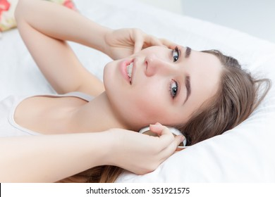 The young beautiful girl in bed listening to music on headphones at home