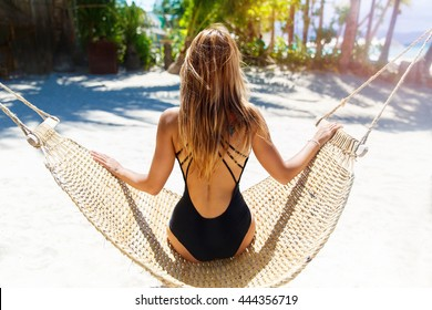 Young beautiful girl in black bathing suit with long blonde hair relaxing in hammock on the tropical beach
