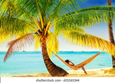 Young beautiful girl in black bathing suit with long black hair relaxing in hammock on the tropical beach on white background