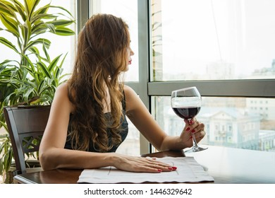 A young beautiful girl in a black dress sits in a restaurant and drinks wine from a glass. close up of young woman which her hand holding with glass red wine as a looking out on the window.