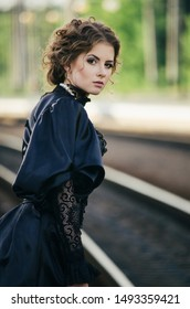 Young beautiful girl in black dress stands on the platform. Perhaps she is going to kill herself. Woman watches someone. She noticed somebody. Pretty girl leans forward. Elegant appearance. Soon train