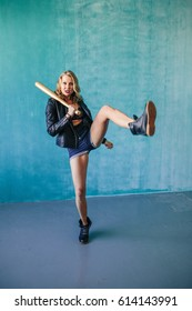 Young beautiful girl in a black jacket in black shoes is standing with a baseball bat on a green background