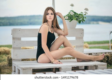 A young beautiful girl in a black swimsuit sits on a white pallet sofa. The girl is sunbathing. She looks aside. Woman leaned on pallet. Straw bales and flowers on the background. She touches her hair
