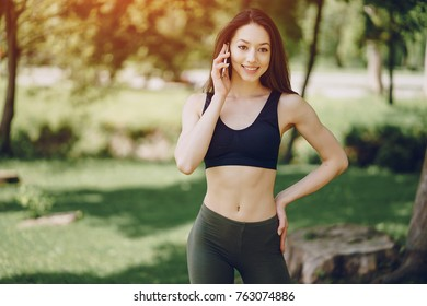 A young and beautiful girl in black toe uses a phone in the nature