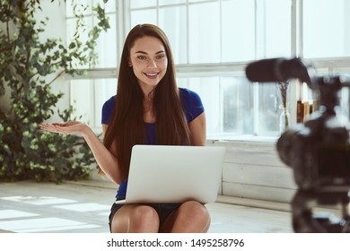 Young beautiful girl blogger stands in front of camera using laptop computer