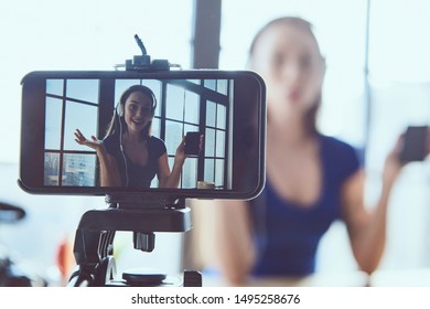 Young beautiful girl blogger working in the office while shooting at camera. Smartphone closeup