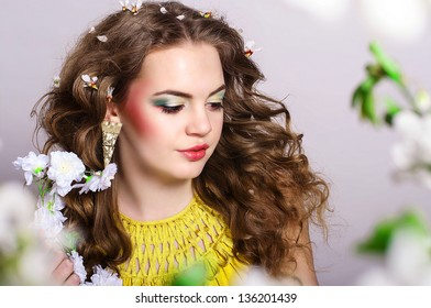 Young beautiful girl with blond curly hair holding flowers