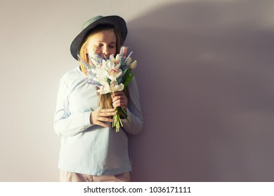 A young beautiful girl with blond dissolved long hair, a felt hat on her head, keeps spring flowers in her hands on a sunny day. Women's Day.
