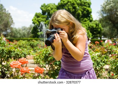Young  beautiful girl the blonde photographs roses with SLR camera