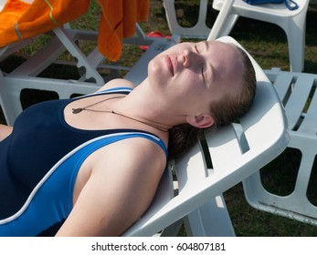 A young beautiful girl in a blue bathing suit rests on the shore of a thermal lake in Heviz. Hungary.