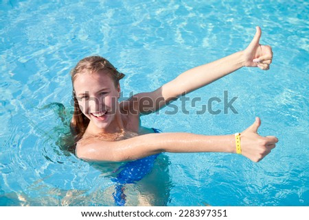 5821ddc14f68d Young beautiful girl in a blue bathing suit enjoys standing in the pool and  showing thumbs