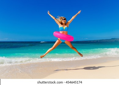 Young beautiful girl in blue bikini having fun on a tropical beach with rubber ring for swimming. Blue sea and sky in the background. Summer vacation concept.