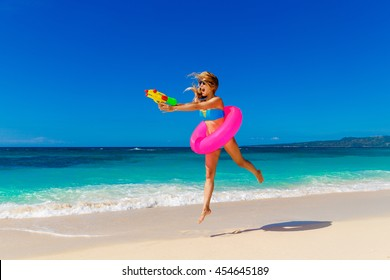 Young beautiful girl in blue bikini having fun on a tropical beach with toy water guns and rubber ring for swimming. Blue sea and sky in the background. Summer vacation concept.